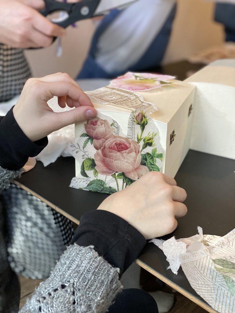 Kinderhände legen Serviettenausschnitte auf Holztruhen