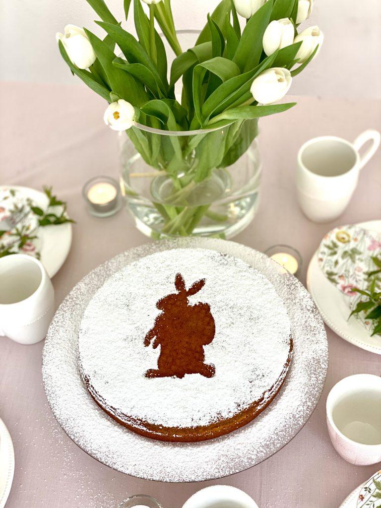 Nochmal der Kuchen von oben auf dem Tisch, mit Tulpen im Hintergrund