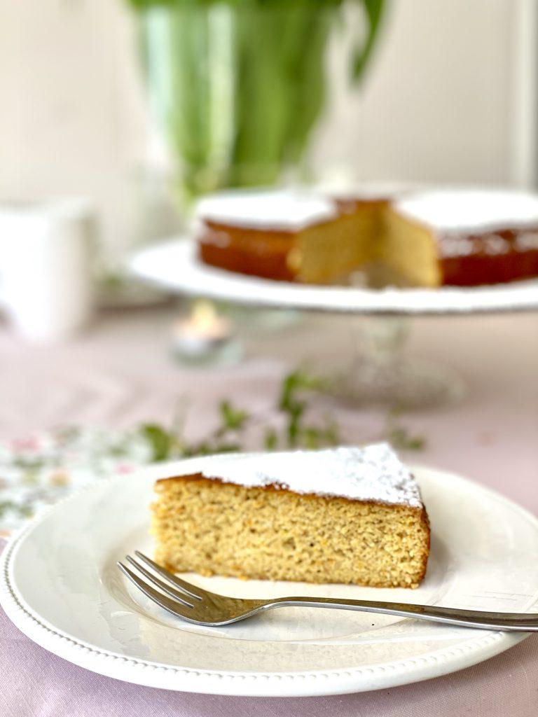 Stück des Orangen-Mandel-Kuchens auf weißem Teller, mit Kuchengabel, vor dem aangeschnittenen Kuchen.