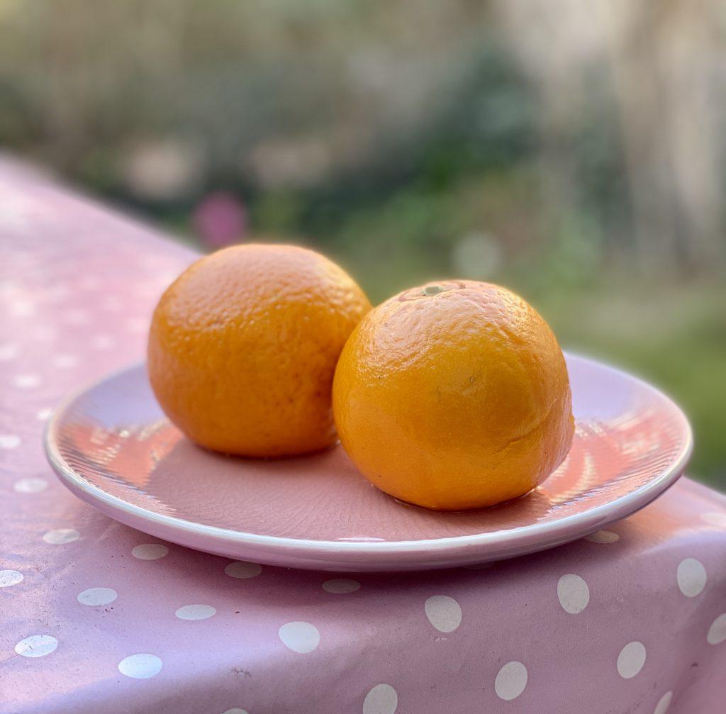 2 Orangen auf Teller auf Gartentisch mit weiß gepunkteter Tischdecke auf rosa.