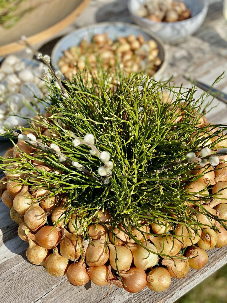 dicker Kranz mit gelben Steckzwiebeln, Blaubeerkraut und Weidenkätzchen