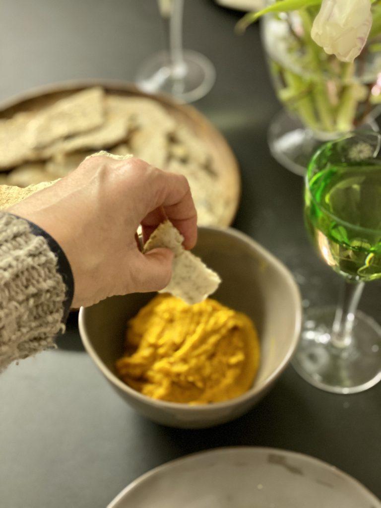 Hand taucht Paleo-Cracker in Gemüse-Dip