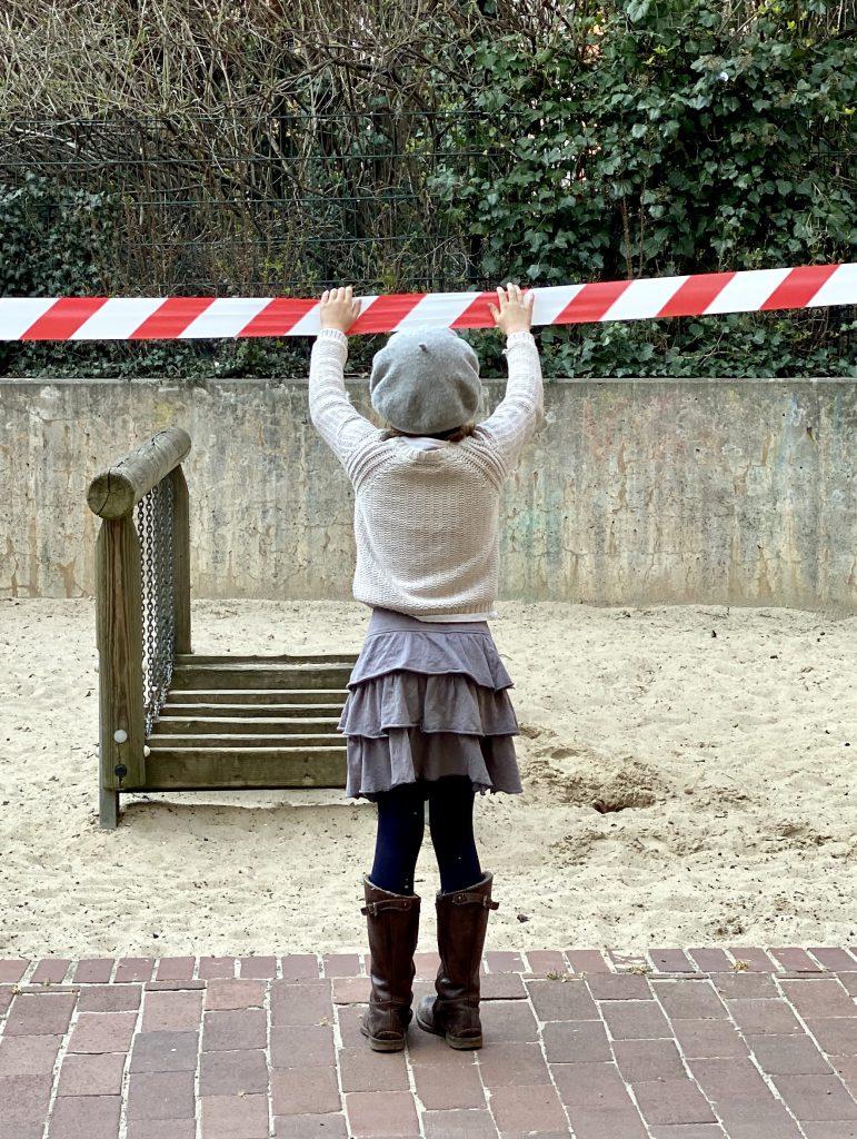 Kind von hinten an Absperrung vom Spielplatz. Das sind harmlose Corona-Sorgen....
