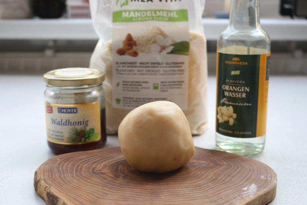 Marzipan-Eier selbst gemacht Zutaten: Honig, gemahlene Mandeln und Orangenwasser. Davor ein Klumpen Marzipan-Masse auf einem Brettchen