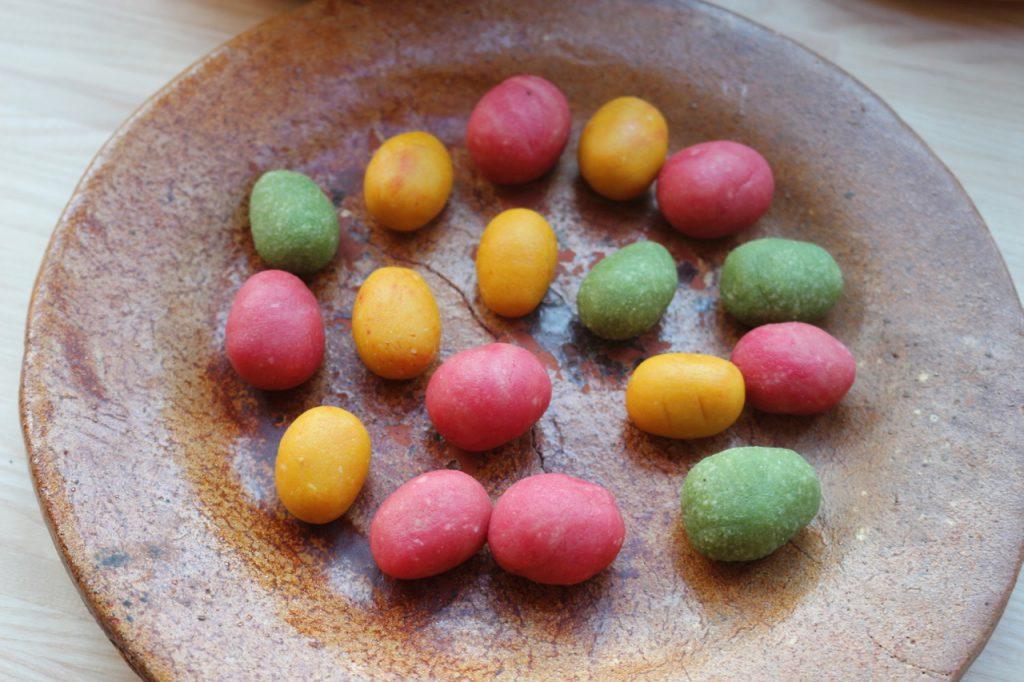 ca. 20 kleine bunte Marzipan-Eier auf braunem Keramik-Teller