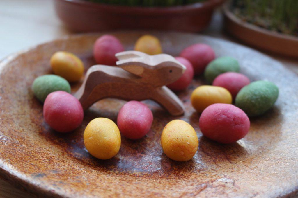 Teller mit bunten Marzipan-Eiern und kleinem springendem Holz-Hasen (Marzipan-Eier selbst gemacht)
