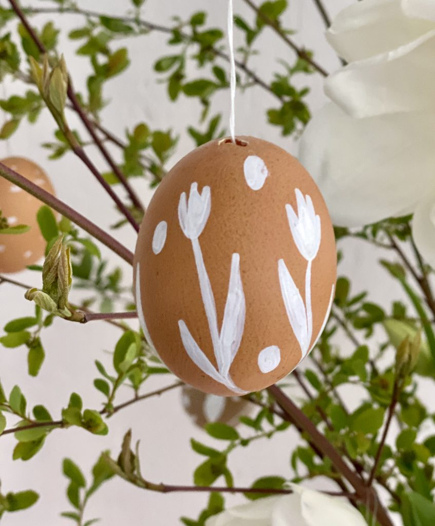 braune Eier am Osterstrauß mit Tulpen