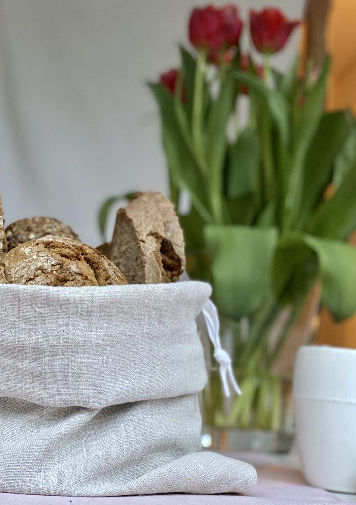 gefüllter Brotbeutel aus Leinen als Brotkorb vor Tulpenstrauß