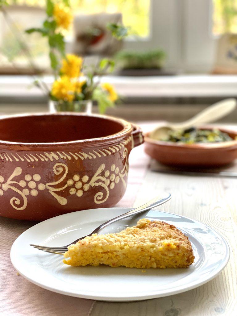 Ein kuchenstückförmiges Stück vom Kürbis-Eier-Auflauf auf einem weißen Teller vor der Auflaufform