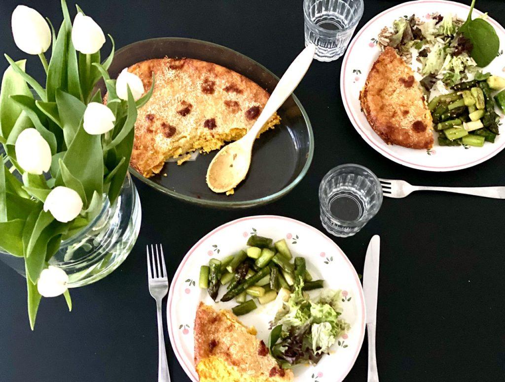 schwarzer Tisch mit Kürbis-Eier-Auflauf, Tellern und weißen Tulpen