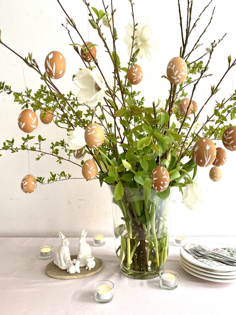 Braune Eier am Osterstrauß an grünen Zweigen in Vase, auf Tisch mit rosa Tischdecke, mit weißen Porzellanhasen neben der Vase