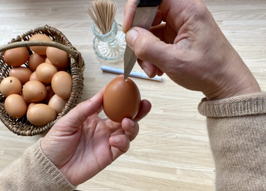 Löcher in die Eier reinmachen: Messer hackt Loch in Ei, um braune Eier am Osterstrauß herzustellen