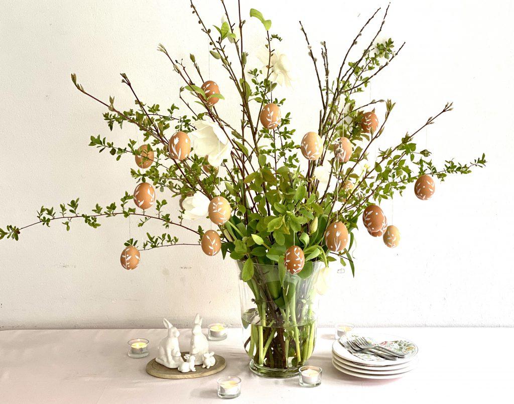 Diverse braune Eier am Osterstrauß an üppigem Frühlingsstrauß mit grünen Zweigen und weißen Blüten