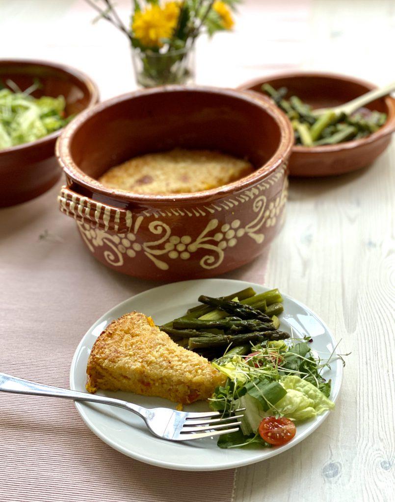 Ein Stück vom Kürbis-Eier-Auflauf auf einem weißen Teller vor der Auflaufform, angerichtet mit Salat und gebratenem grünem Spargel