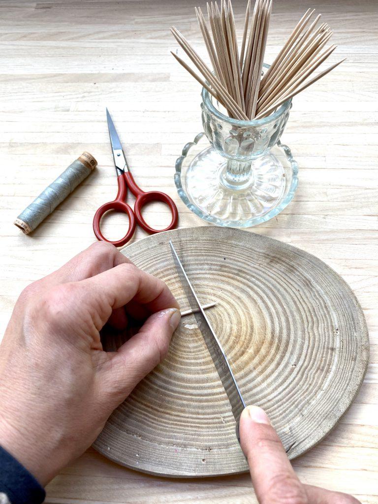 Mit Messer Kerbe in Zahnstocher schneiden, um braune Eier am Osterstrauß herzustellen