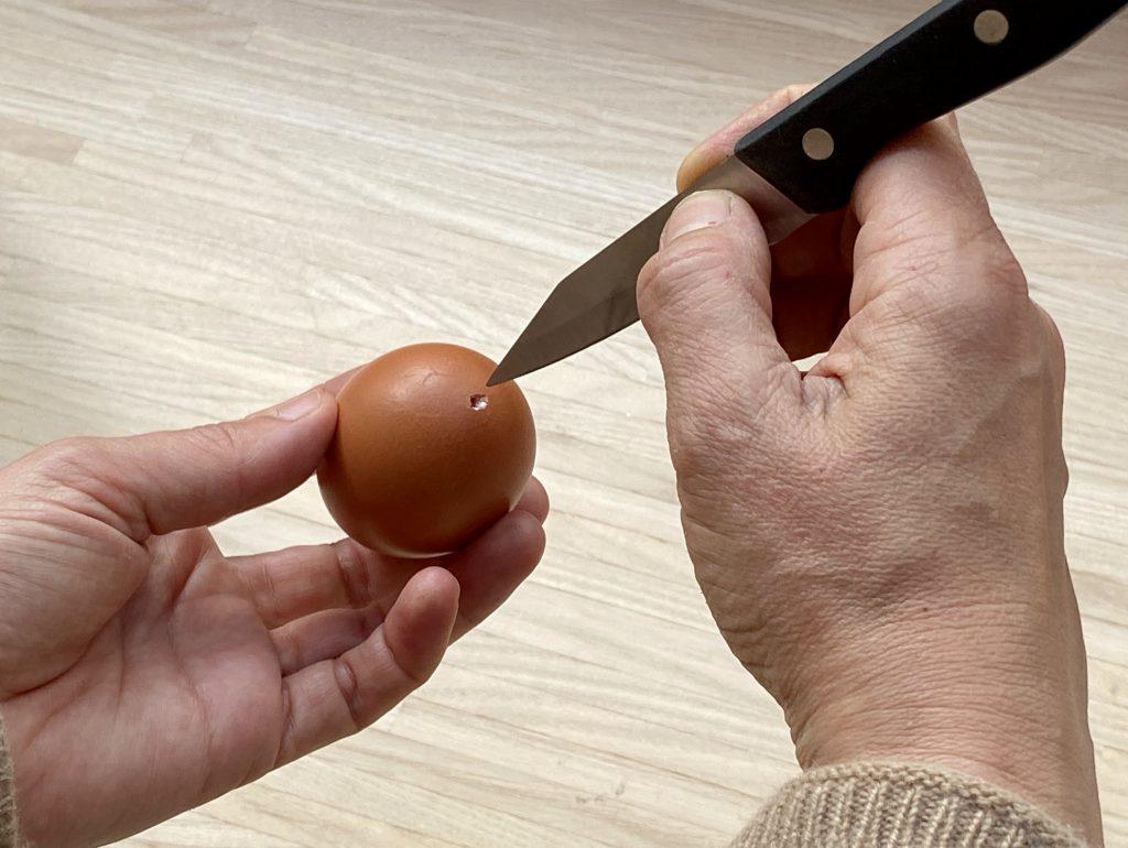 Messer hackt Loch in Ei