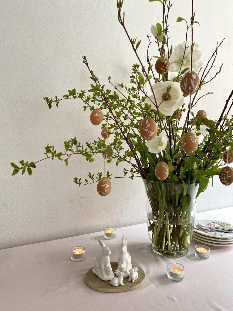 braune Eier am Osterstrauß, mit aufgeblühter Magnolie