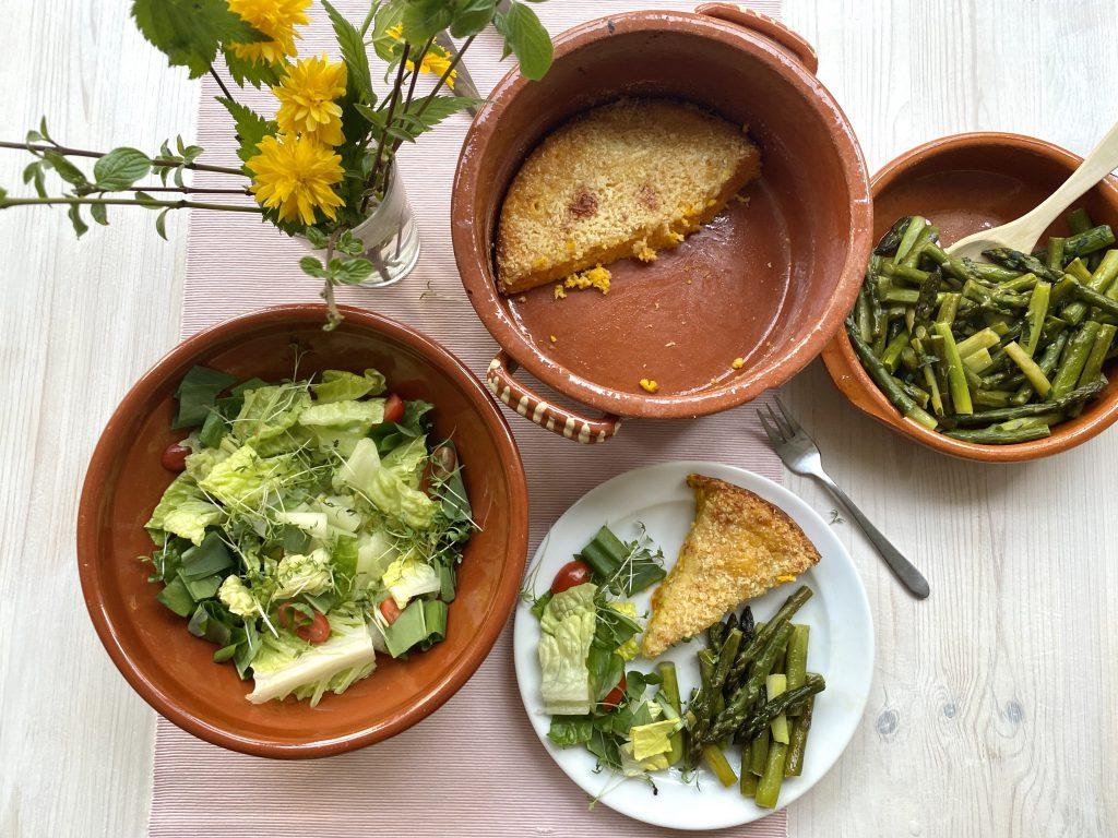 gedeckter Tisch mit Auflaufform (nur noch halb gefüllt), Teller, Salat und grünem Spargel
