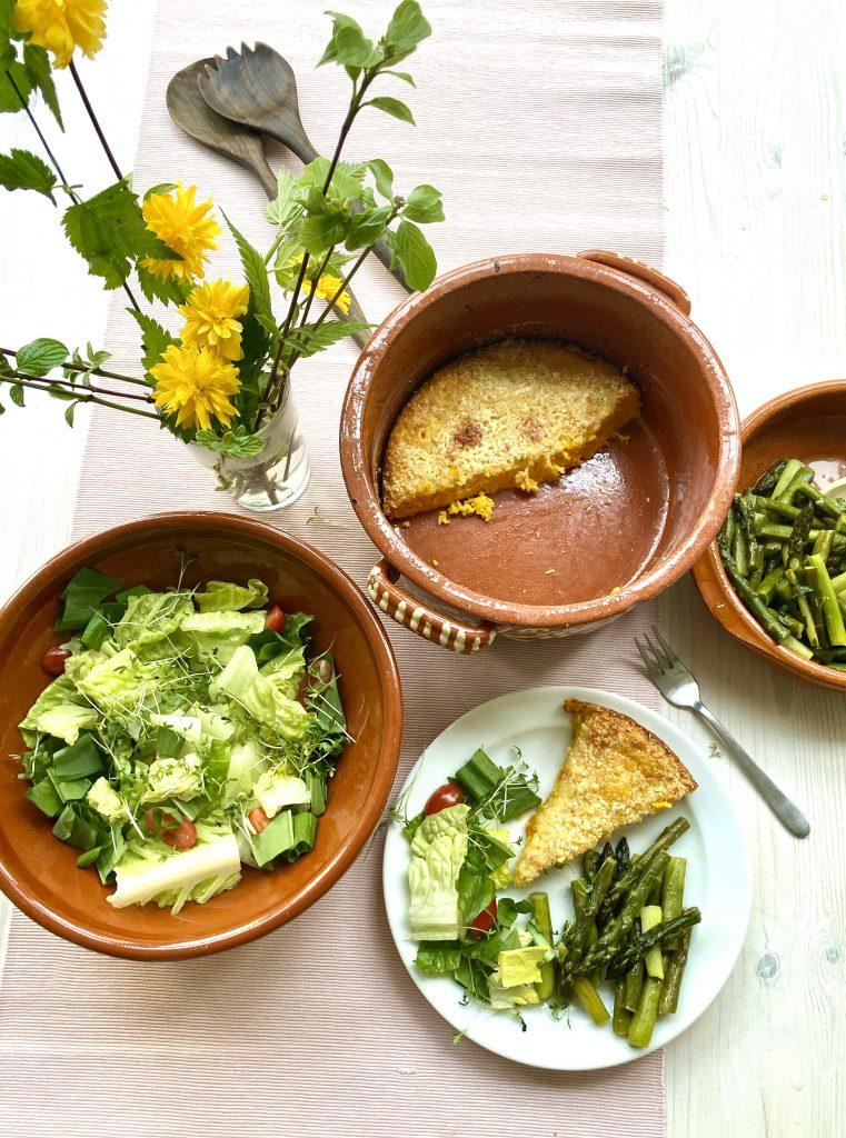 Ein Stück vom Kürbis-Eier-Auflauf auf einem weißen Teller neben Auflaufform, Salatschüssel und Schüssel mit grünem Spargel, von oben aufgenommen