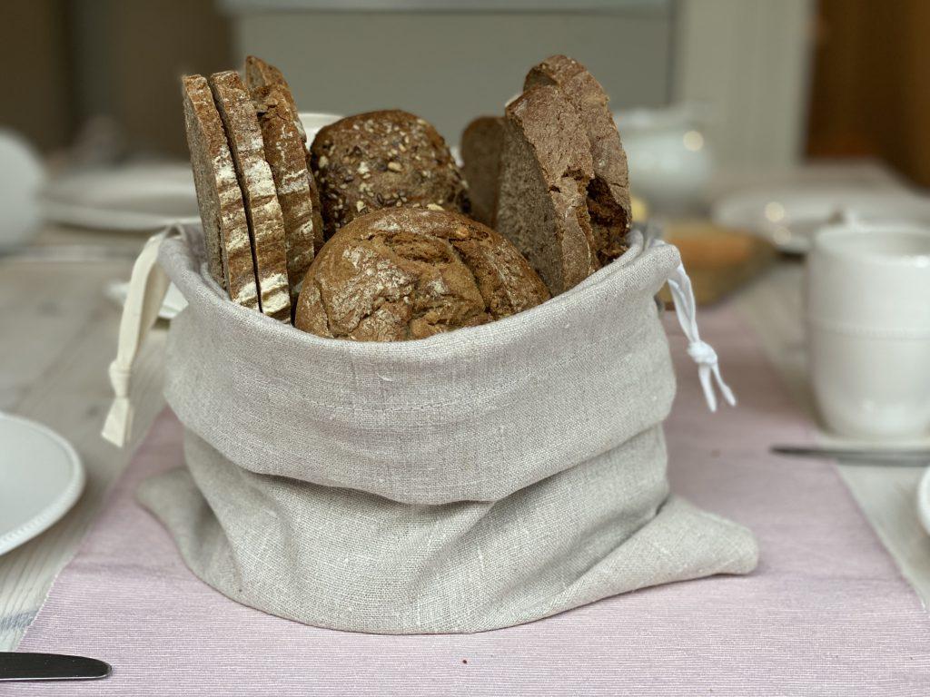 Brotbeutel aus Leinen als Brotkorb auf Frühstückstisch, mit Vollkornbrötchen und Brot drin
