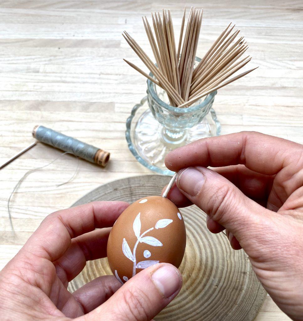 Hölzchen ins Loch im Ei stecken, um braune Eier am Osterstrauß aufhängen zu können