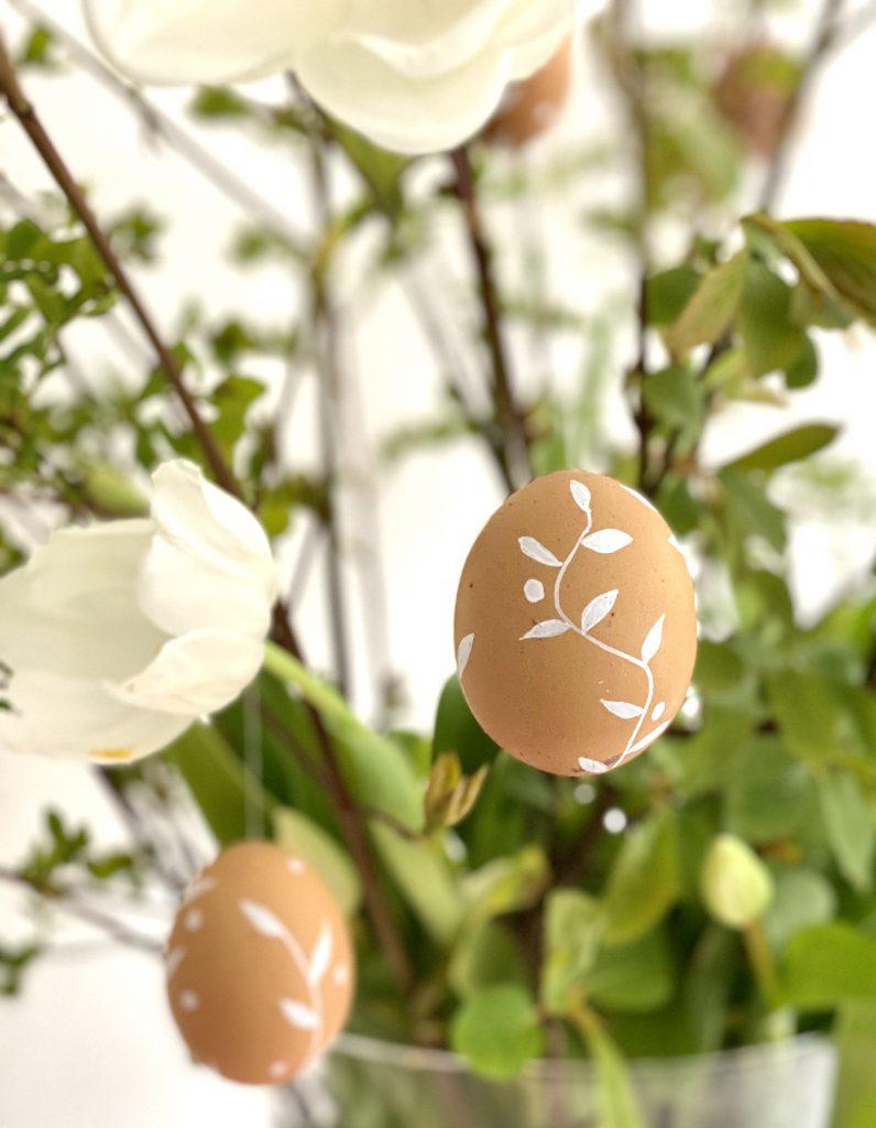 braune Eier am Osterstrauß mit Blumenranken und Punkten