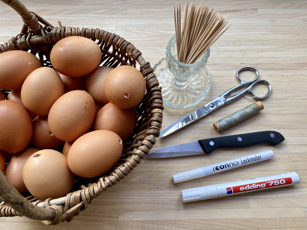 Korb mit ausgeblasenen Eiern und alles benötigten Materialien, um braune Eier am Osterstrauß herzustellen