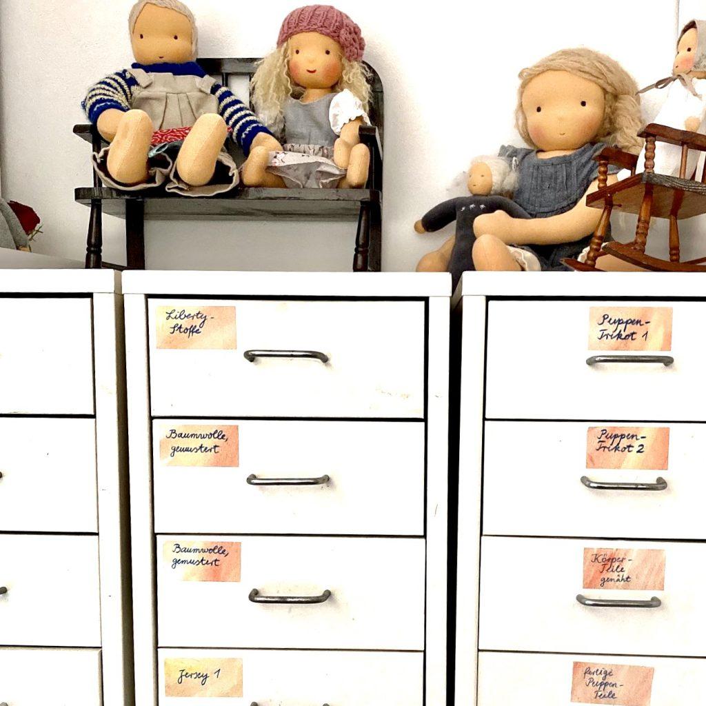 Schubladenschrank mit Puppen darauf. Jede Schublade trägt eine Beschriftung, was drin ist. Ordnung schaffen ist auch etwas Gutes an der Corona-Krise.