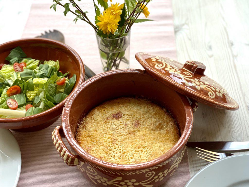Kürbis-Eier-Auflauf in Ton-Gefäß auf gedecktem Tisch, daneben ein grüner Salat