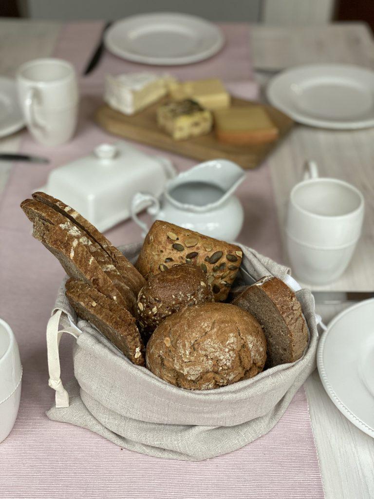 Mit Brot gefüllter Brotbeutel aus Leinen auf Frühstückstisch mit Käseplatte