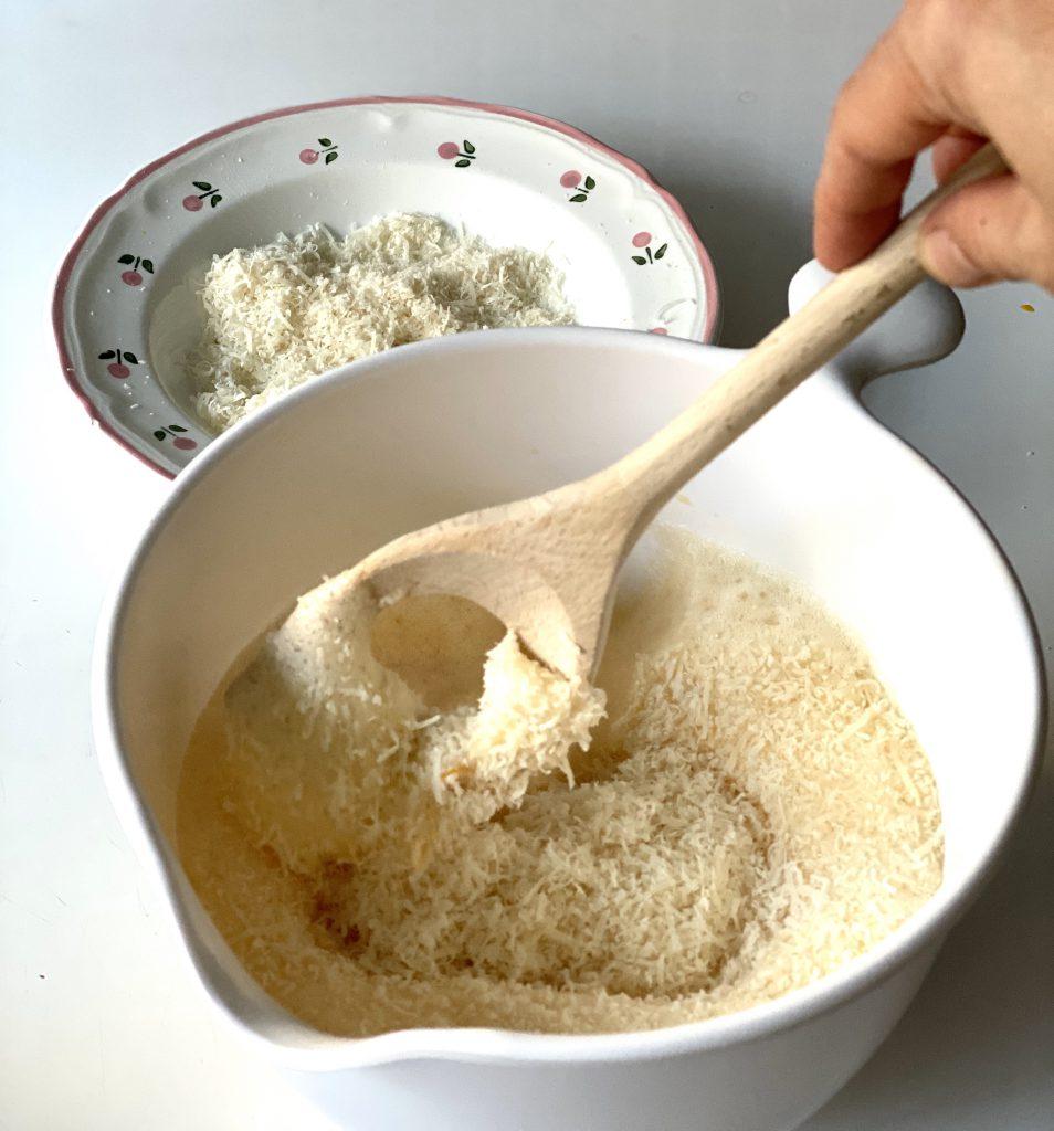 Holzlöffel mit Loch rührt geriebenen Parmesan in geschlagene Eier