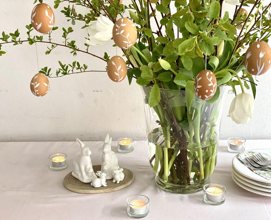 braune Eier am Osterstrauß, Strauß auf Tisch mit rosa-weißen Gedecken