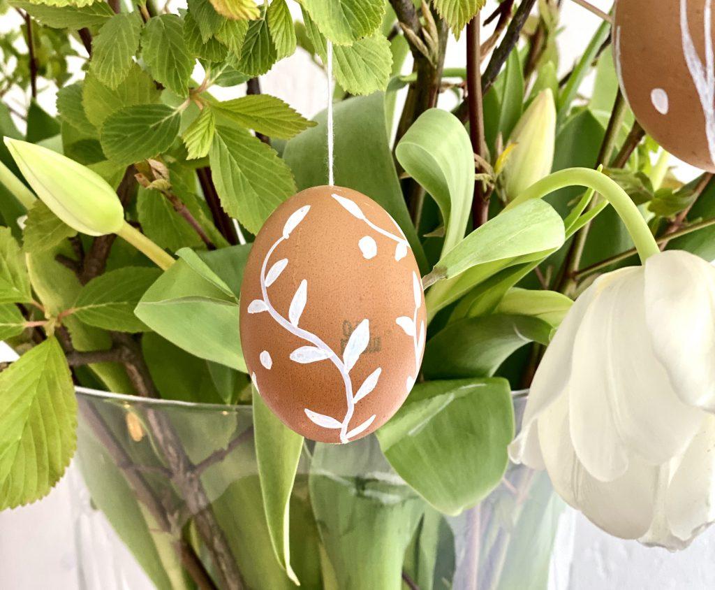 Braune Eier am Osterstrauß mit weißer Verzierung (Blumenranke)