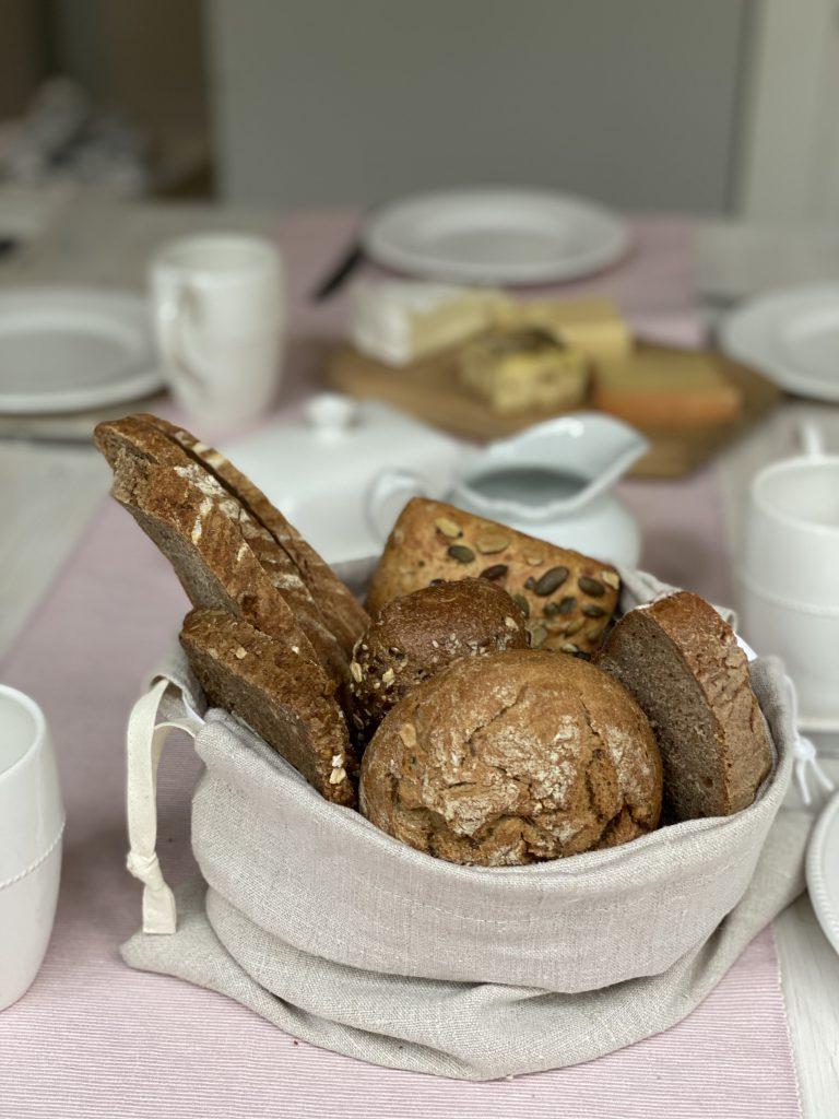 Frühstückstisch mit Brotkorb aus Leinenbeutel