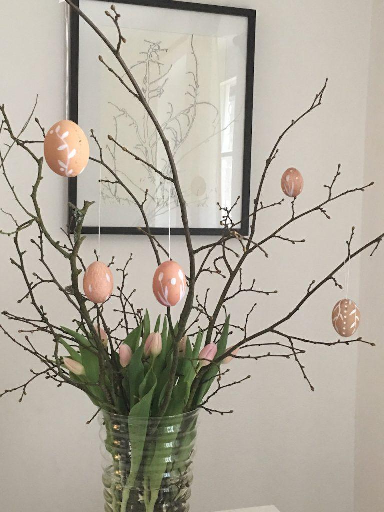 Glasvase mit Obstbaumzweigen, weiß verzierten Eiern dran und rosa Tulpen - auch eine Idee für braune Eier am Osterstrauß!