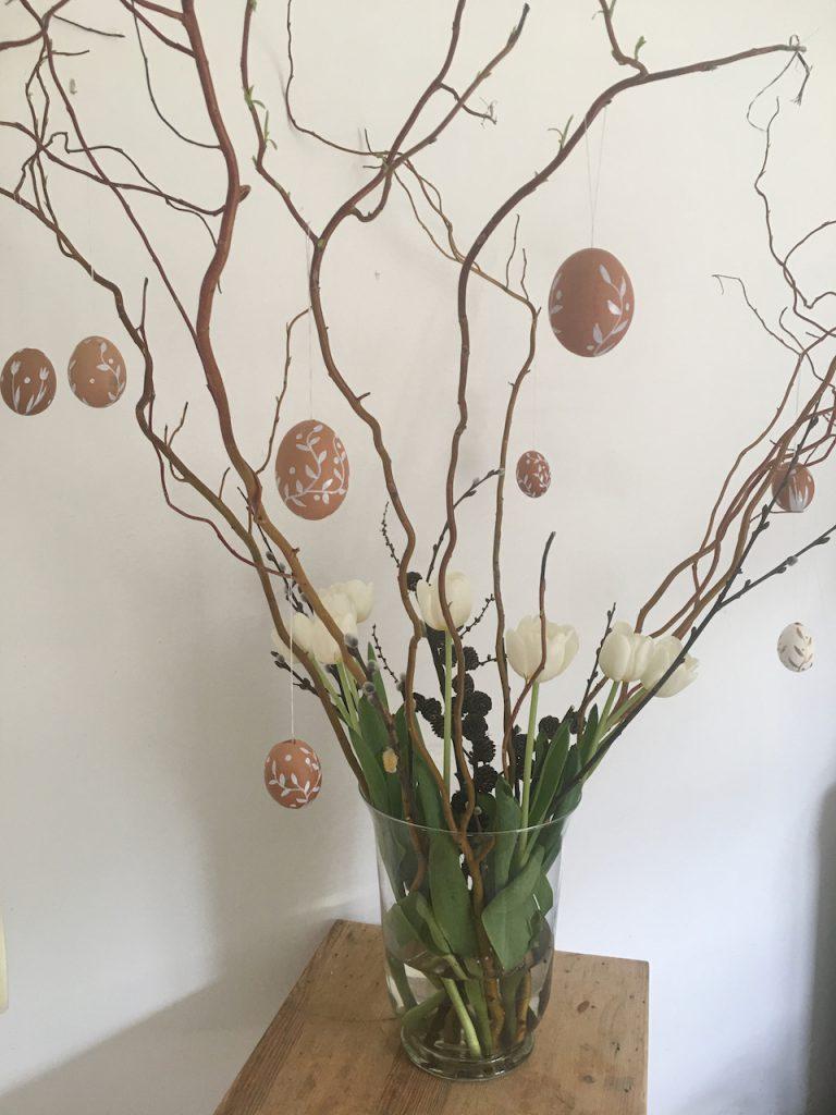 kahle Weidenzweige mit weiß verzierten Eiern daran und weißen Tulpen in Glasvase