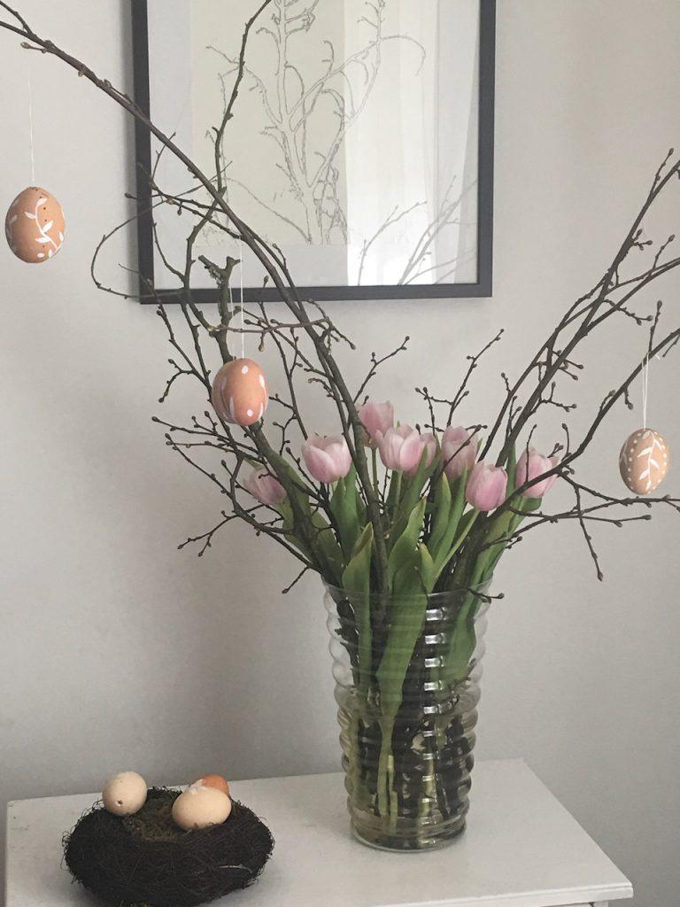 verschiedene weiß verzierte Eier an Obstbaumzweigen mit rosa Tulpen