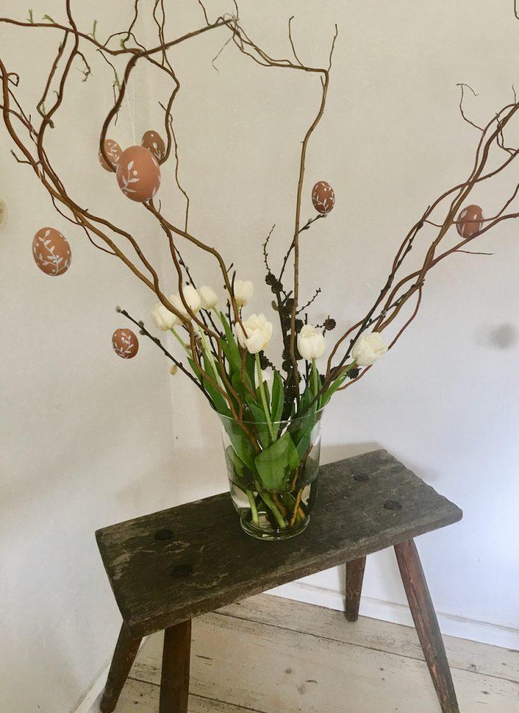 kahle Weidenzweige mit weiß verzierten Eiern daran und weißen Tulpen in Glasvase, auf rustikalem Bauernhocker