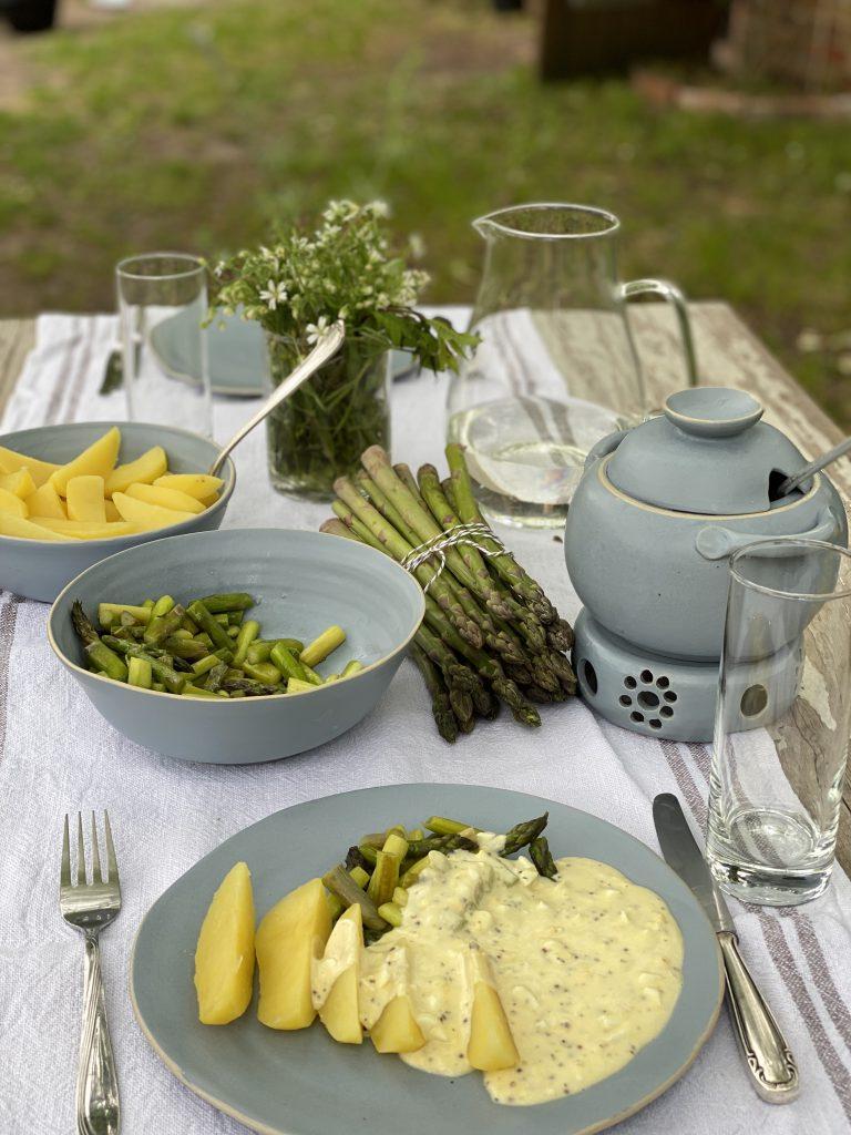 Gedeckter Tisch mit angerichtetem Spargel auf teller mit Sauce und Kartoffeln