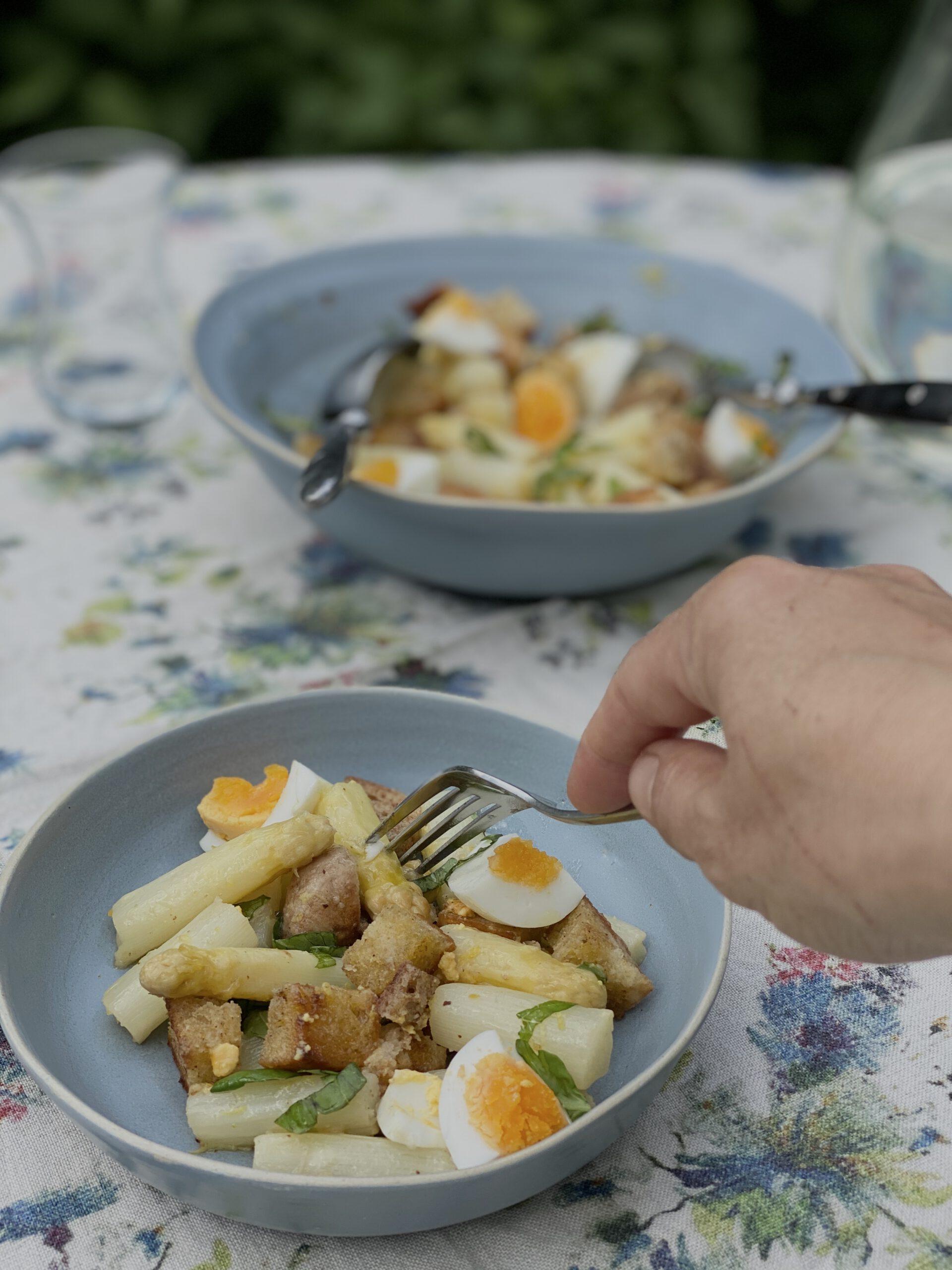 Mit der Gabel in eine Portion Spargel-Panzanella. Im Hintergrund die Servierschüssel auf dem Gartentisch