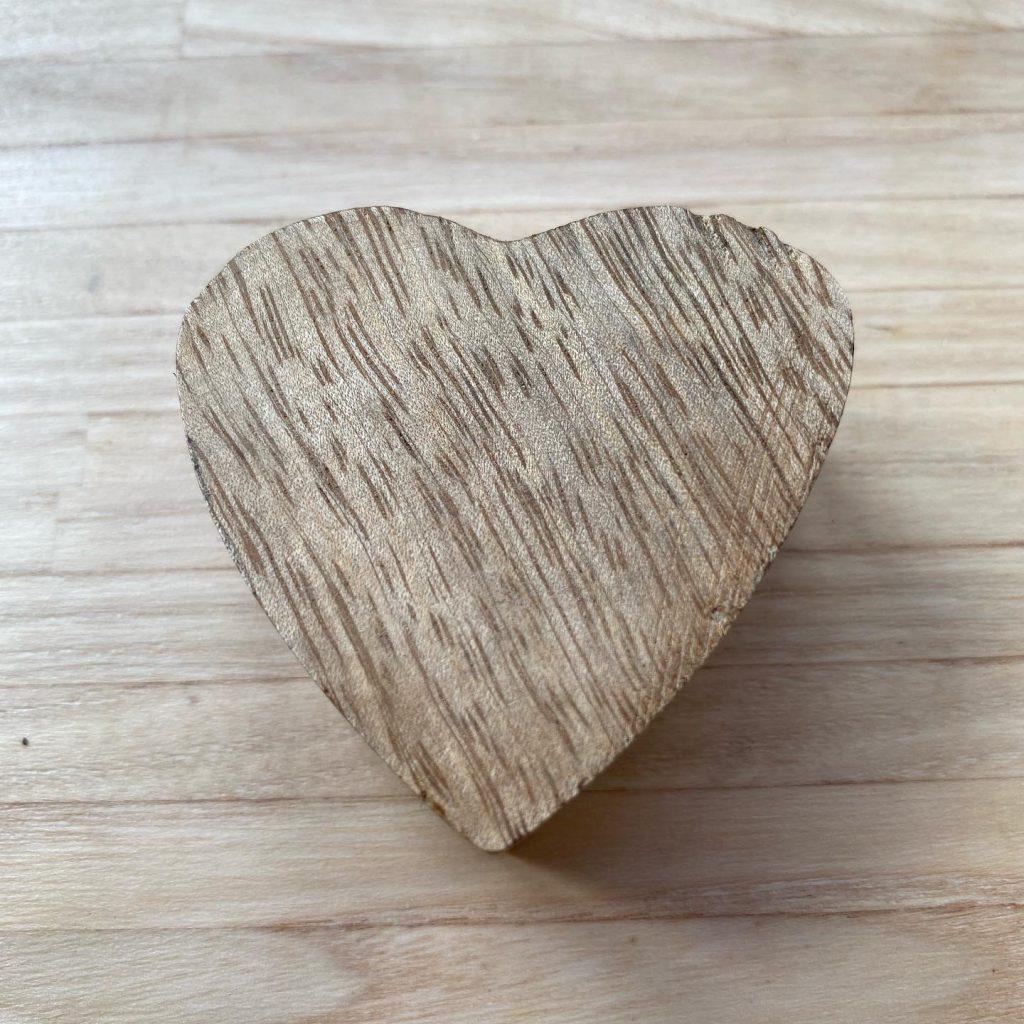 Glück sehen lernen: Herz aus Holz auf Holz
