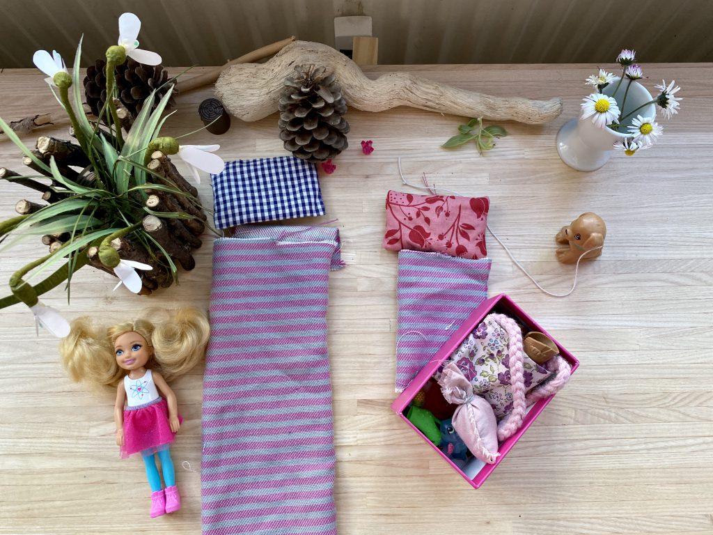 """Kreativ mit Barbies spielen: Selbst genähte Schlafsäcke für die Barbies und Blumendekoration rund um den """"Campingplatz""""."""
