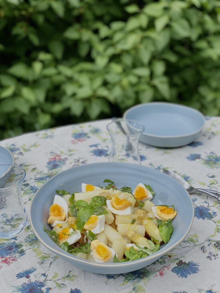 Hellblaue Schüssel mit Spargel-Panzanella auf Gartentisch vor Fliederbusch
