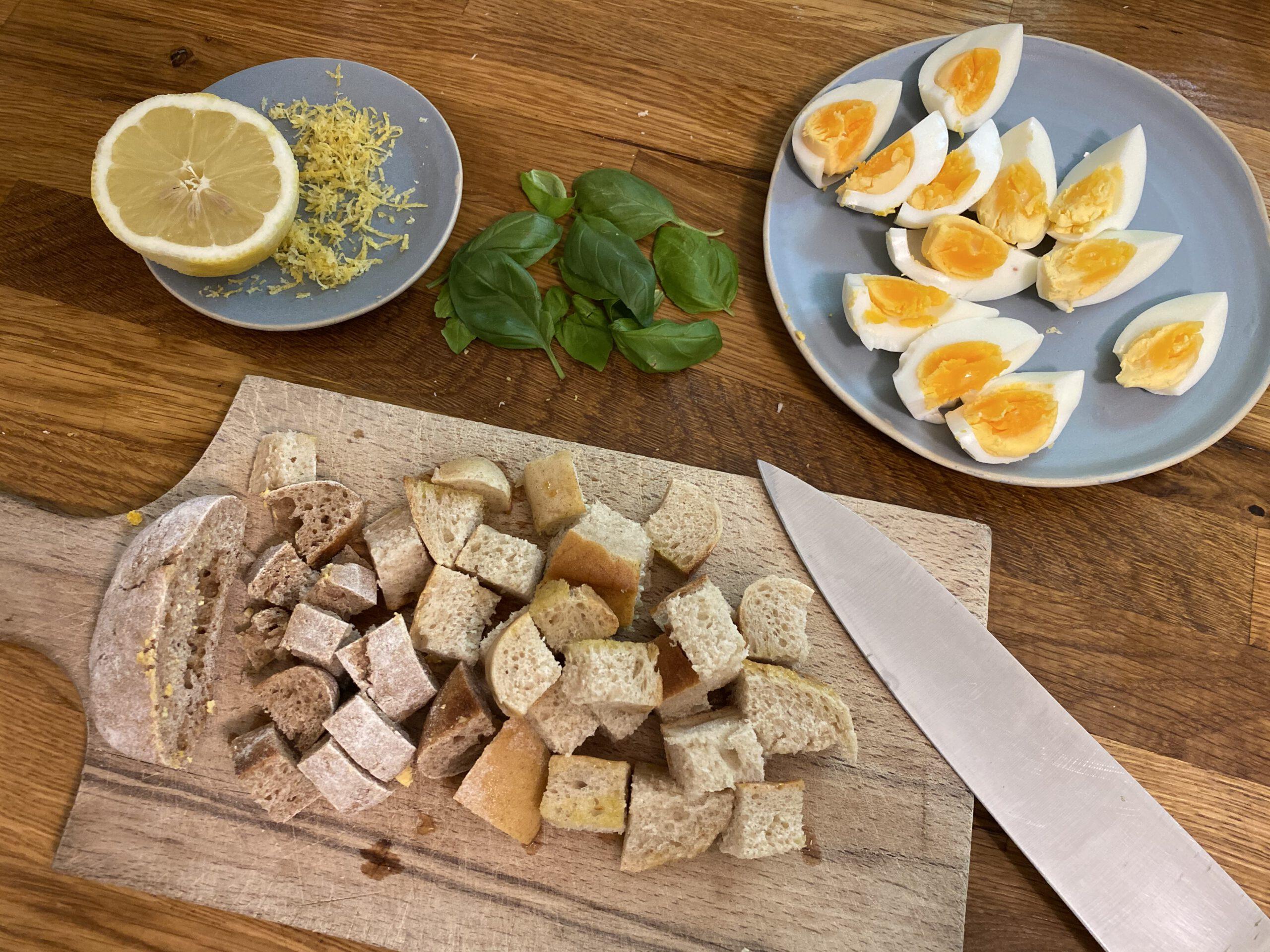 Für eine Spargel-Panzanella schneidet man gerösteten Brot in Würfel und Eier in Achtel.