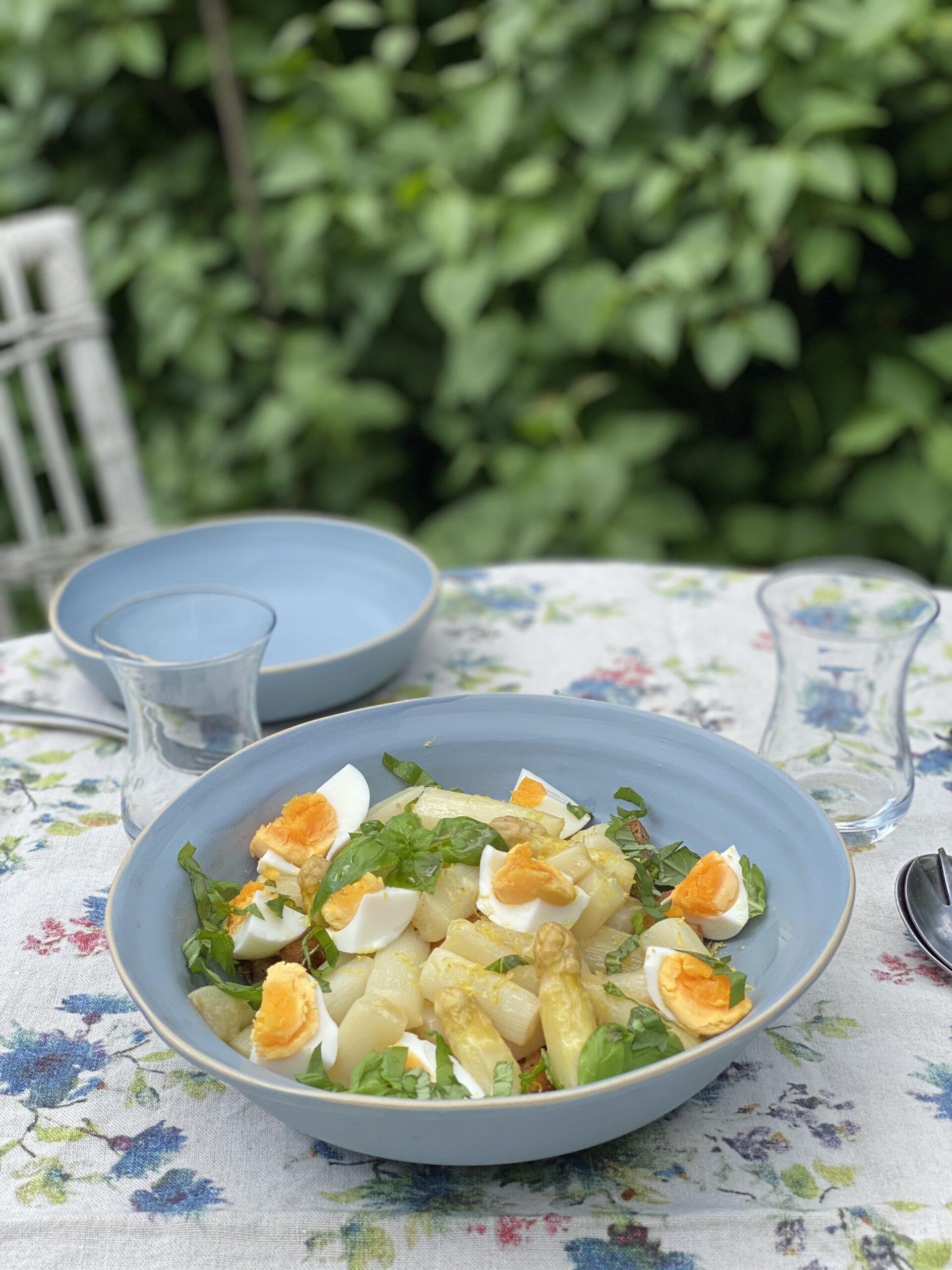 Hellblaue Schüssel mit Spargel-Panzanella auf Gartentisch vor Flieder
