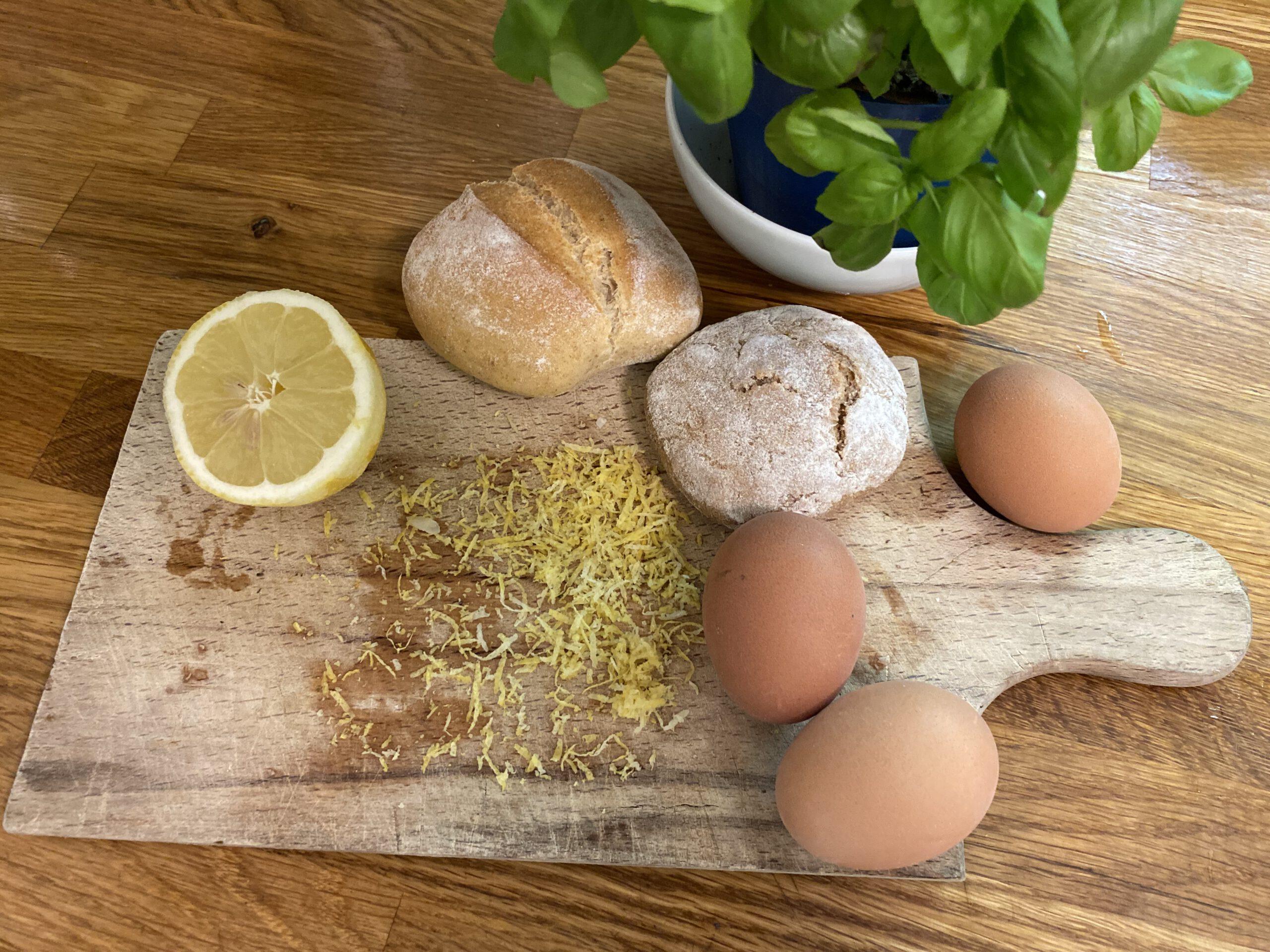 Brett mit geriebener Zitronenschale, altbackenen Brötchen und gekochten Eiern für die Spargel-Panzanella