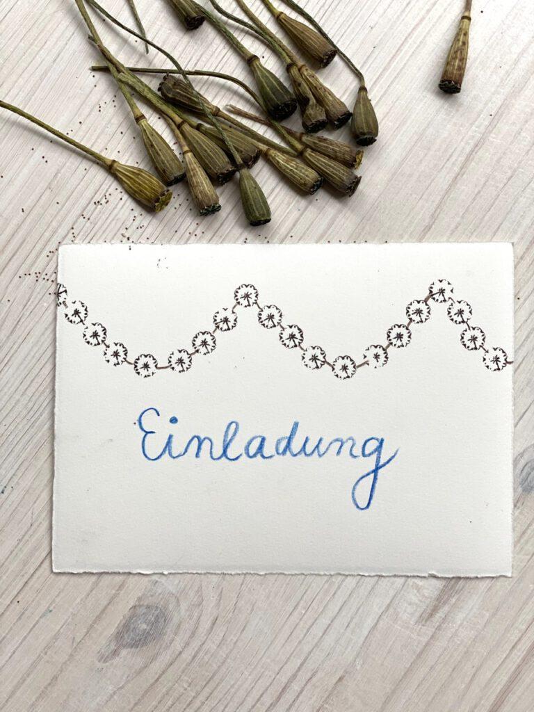"""Karte mit Schriftzug """"Einladung"""" in blauer Schreibschrift, dazu Girlande aus Stempeln mit Mohnkapseln"""