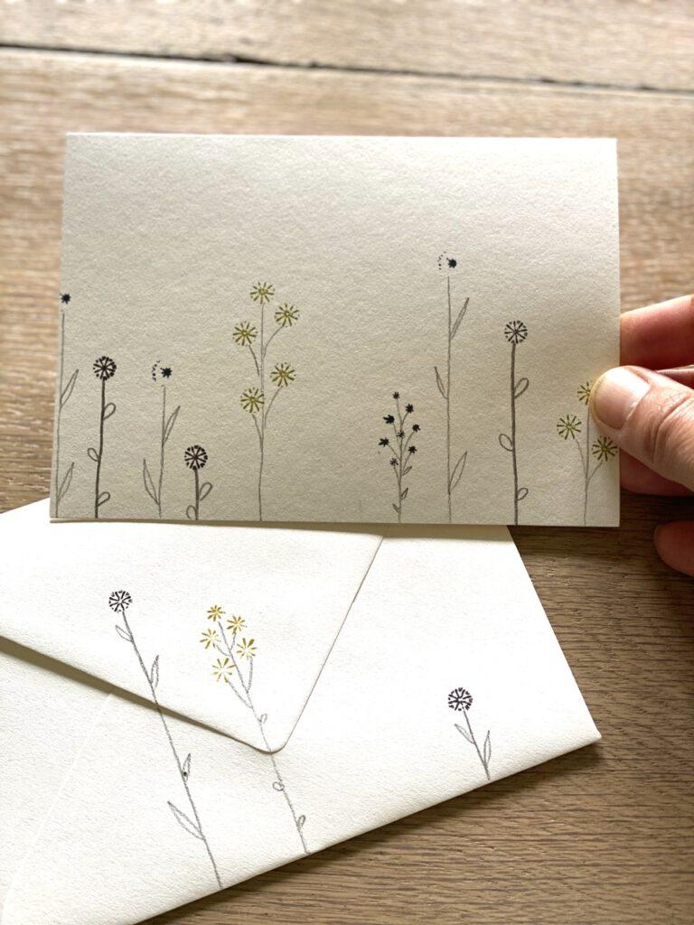 Ein ganz besonderer der Glücksmomente der Woche vom 25. Juni bis 1. Juli 2020: Eine weiße Karte mit Mohnstempeln verschiedener Formen, mit Bleistift zu einer zarten Blumenwiese ergänzt