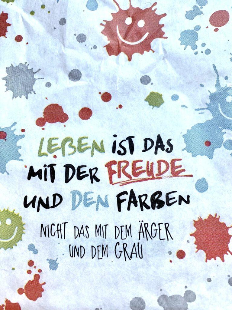 """Glücksmomente der Woche vom 11. bis 17. Juni 2020, Glücksmoment 4: Foto der Papiertüte mit dem Spruch """"Leben ist das mit der Freude und den Farben, nicht das mit dem Ärger und dem Grau."""""""