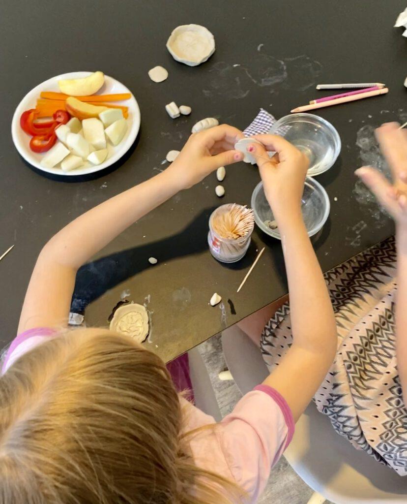 Zwei Kinder von oben kneten mit Modelliermasse auf schwarzem Tisch